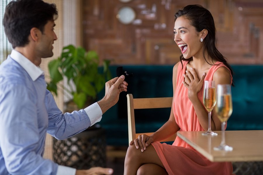 Man proposing to woman offering engagement ring in restaurant