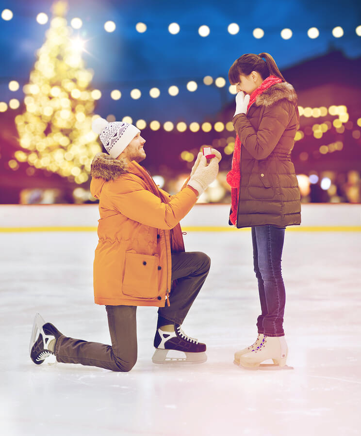 A man proposing to a woman on one knee while ice skating on an ice rink