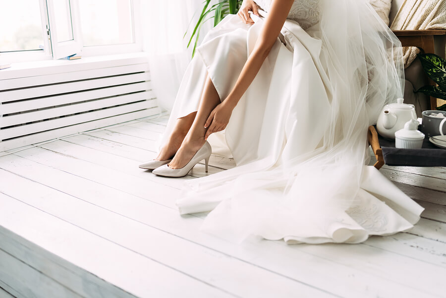 A bride putting her shoes on for her wedding