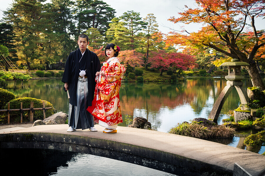 A traditional Japanese bride and groom wearing an iro-uchikake and a montsuki