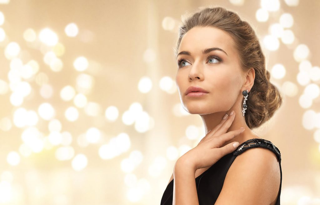 a woman wearing luxury diamond earrings with a background of lights