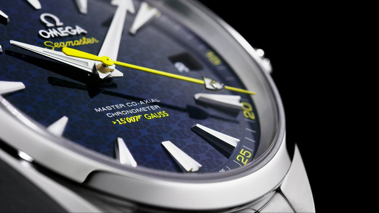 James Bond's iconic coat of arms features patterned on the striking blue dial and at the tip of the bright yellow second hand.