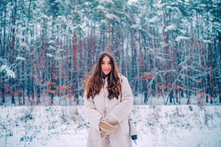 A woman stood in a snowy woods