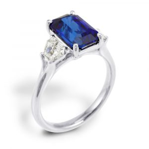 A platinum 3.32ct emerald cut sapphire and 0.62ct diamond three stone ring
