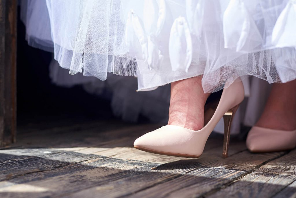 A bride's nude shoe and the bottom of her white dress