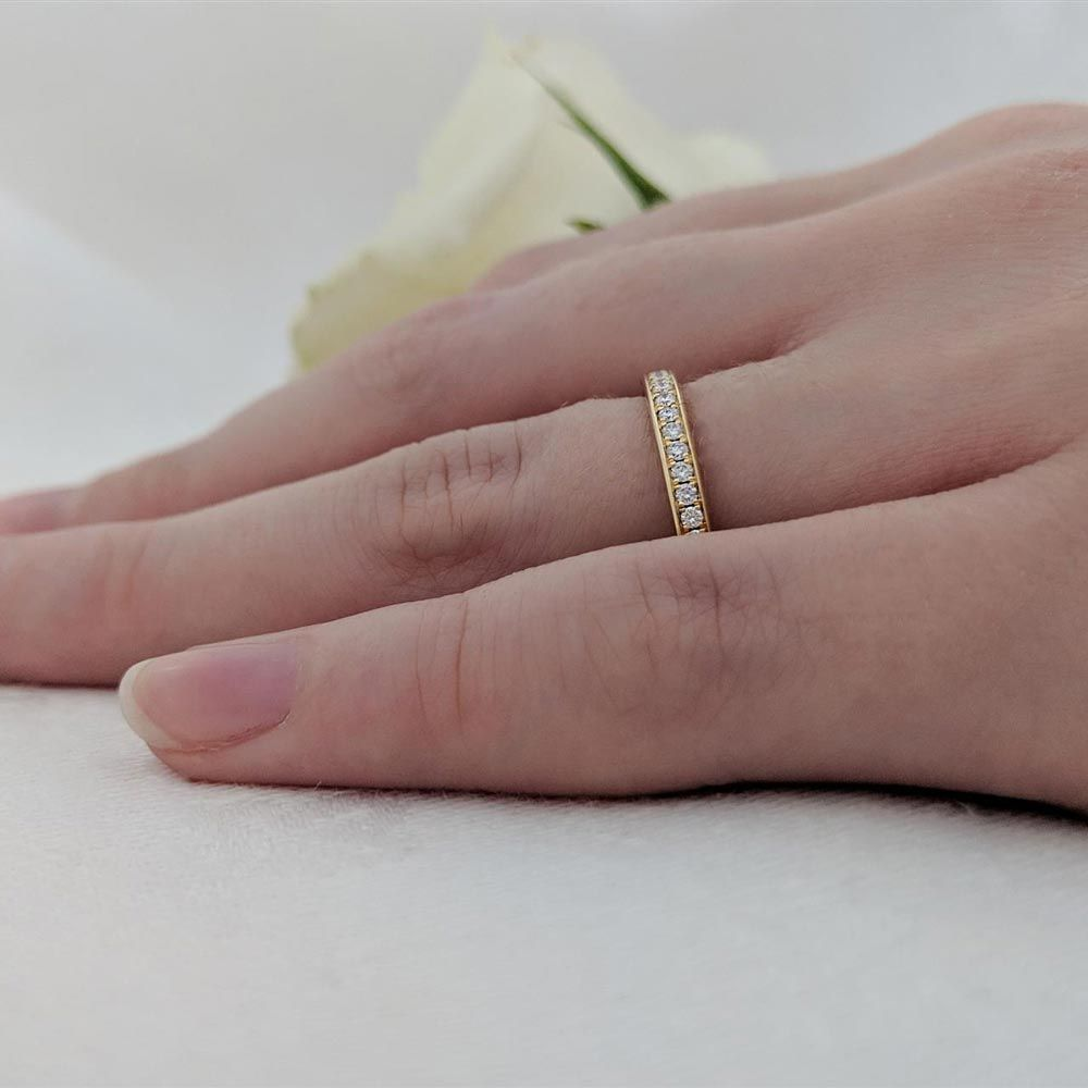 The 18ct yellow gold Memoire 0.15ct round brilliant cut diamond eternity ring worn on a finger